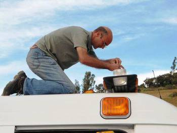 Markus Rolli on top of an ambulance, fixing a defective light.
