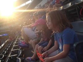 At the ballgame. Notice that Sarah is totally into the game. Our youngest watched more intently than any of the older siblings.