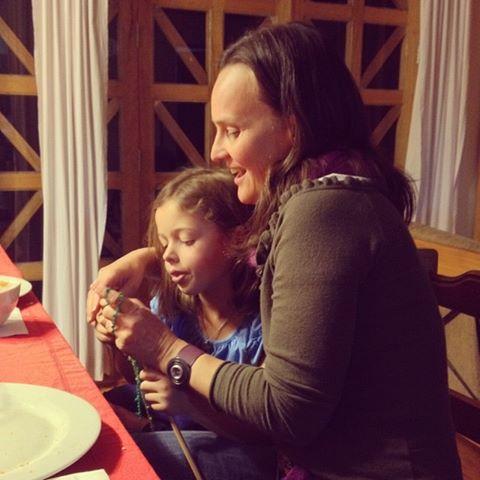 Damaris teaches Annie to knit.