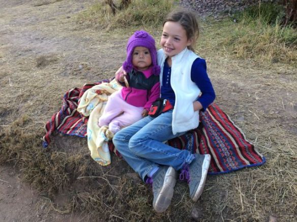 """Lots of Quechua people will find the look of our children interesting.  They especially like the look of Sarah, who is a little more blond than the others with her big, blue eyes.  They will ask to put their kids in pictures with Sarah; sometimes she says """"Yes"""", but often she will say """"No"""".  I leave the decision up to her.  Annie, in maybe a classic older sister move, will often sit in for Sarah in these situations so that the people asking will not be disappointed.  This is a picture of Annie sitting with a little Quechua girl that Sarah refused to be pictures with.  Look at those big cheeks on that little toddler!"""