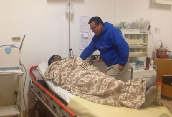 Agustin giving prayer and comfort to a man dying of liver and renal failure.