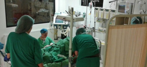 In the ICU. Anesthesiologist Dr. Susan Dressler kneeling next to the bed.